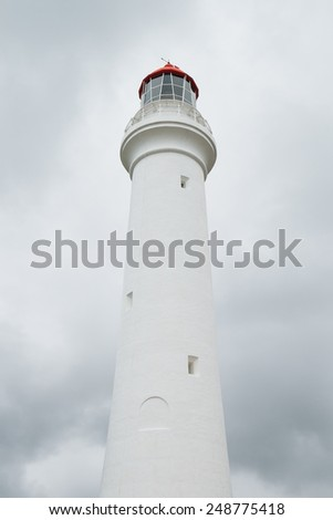 White lighthouse in front of storm clouds - stock photo