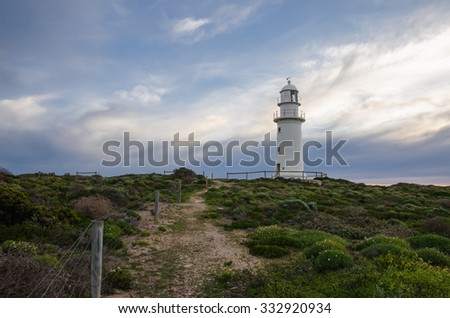 White lighthouse on background of cloudy sky