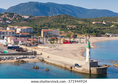 White lighthouse tower with green light in Port of Propriano, South region of Corsica island, France