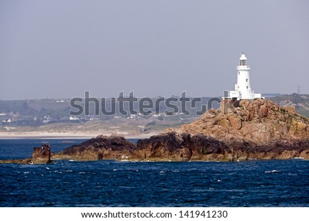 White lighthouse; white lighthouse on jagged rocky outcrop in deep blue sea; shore-line visible in distance; good copy-space over pale blue sky  - stock photo