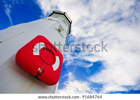 White lighthouse with a red life preserver against a cloudy blue sky on a bright winter morning. Photo taken in Anstruther, Scotland.
