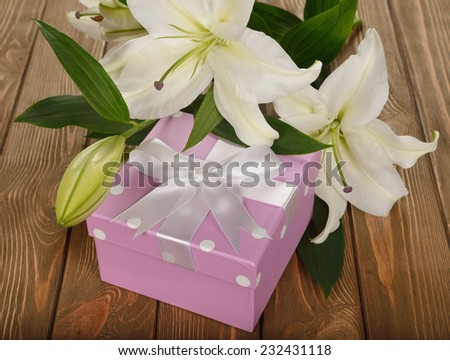 White lily and a box on a brown background