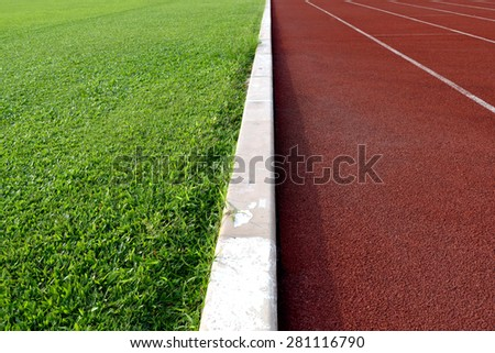 white line between green grass football field and track runway - stock photo