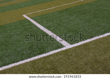 white line on green plastic football field in a middle school