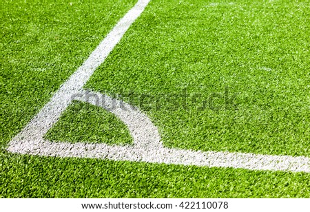 White lines marking on green grass in the corner of the soccer or football field