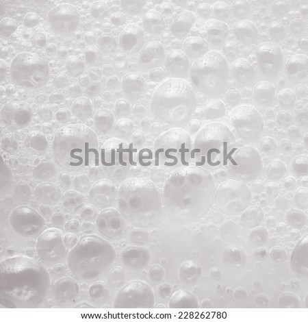 White liquid soap foam with air bubbles background texture closeup. Square format - stock photo