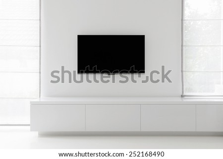 white living room detail tv on wall with commode and epoxy flooring - stock photo