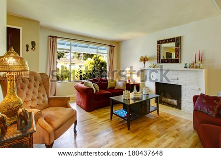 White living room with a brick background fireplace, black coffee table, burgundy love seats and antique chair. View of the dining area