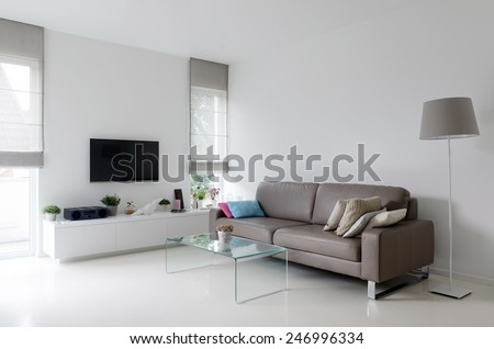 White living room with taupe leather sofa and glass table - stock photo