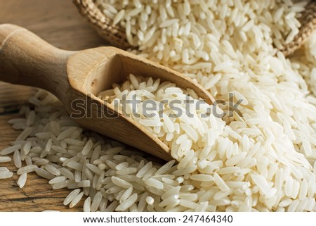 White long rice on wooden spoon - stock photo