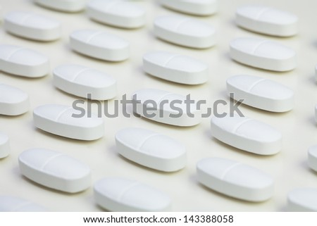 White long tablet drugs laying in a row pattern on white table