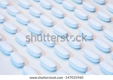 White long tablet drugs laying in a row pattern on white table under laboratory light