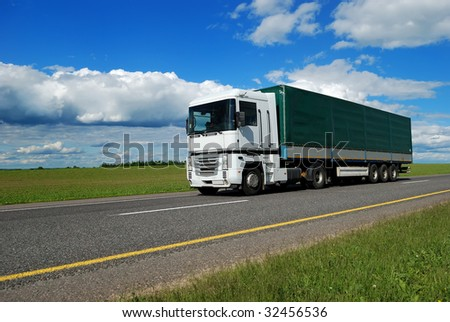 white lorry with green trailer on the highway over blue cloudy sky - stock photo