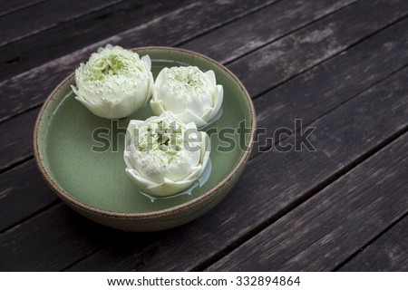 White lotus flower floating in green bowl with space on wood floor - stock photo