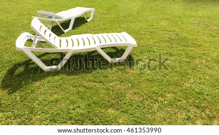 White loungers green grass lawn, outdoor chaise-longue vacation relaxation furniture