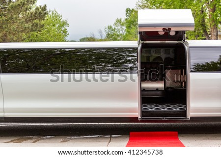 White luxury limousine with open up door and red carpet leading to. - stock photo