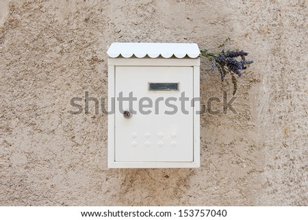 White mailbox on beige stucco wall in a box bouquet of lavender