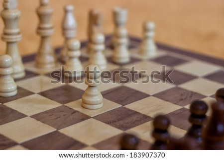 White make the first move in chess. Chess pieces on a table in the room, wood Chess Set - stock photo