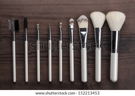 white make-up brushes on brown wooden table