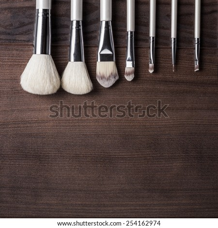 white make-up brushes on brown wooden table - stock photo