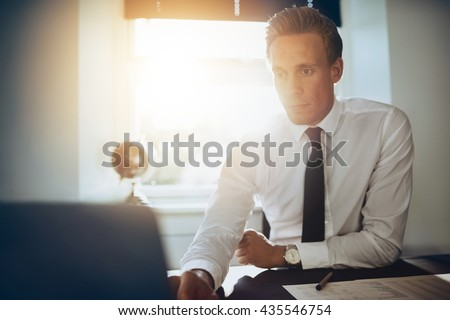 white male executive business man working at his laptop sitting at his desk in a white shirt and black tie - stock photo