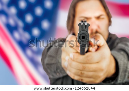 White male holding a handgun with the american flag as a backdrop. - stock photo