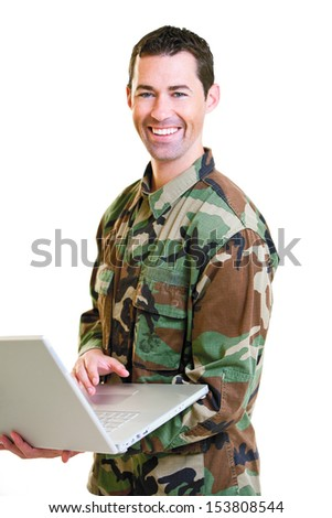 White male in army uniform on lap top smiling isolated on white background. - stock photo