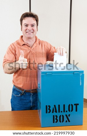 White male mid adult voter dropping his ballot in the box and giving a thumbs up.   - stock photo