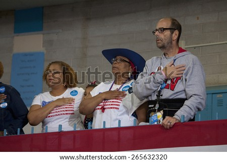 White man and black woman put hand on heart for pledge of allegiance at President Obama campaign rally at Orr Middle School in Las Vegas, October 26, 2012  - stock photo