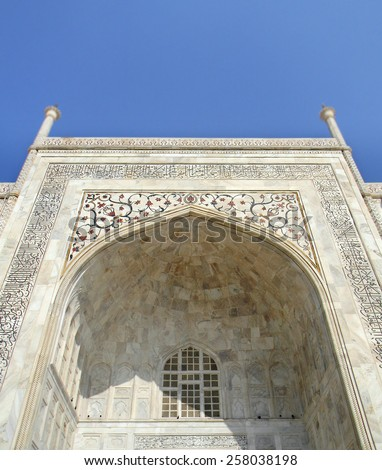 White marble details of the Taj Mahal mausoleum in Agra, India, with floral inserts and Koran verses - stock photo