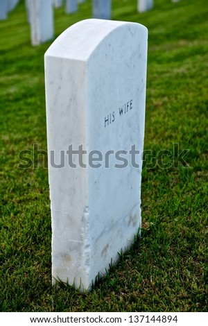 "White marble headstone or grave marker with ""HIS WIFE"" engraved in black lettering in a cemetary"