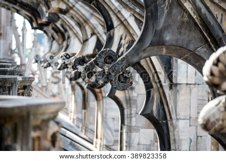 White marble statues on the roof of famous Cathedral Duomo di Milano on piazza in Milan, Italy  - stock photo