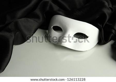 White mask and black silk fabric, isolated on white - stock photo