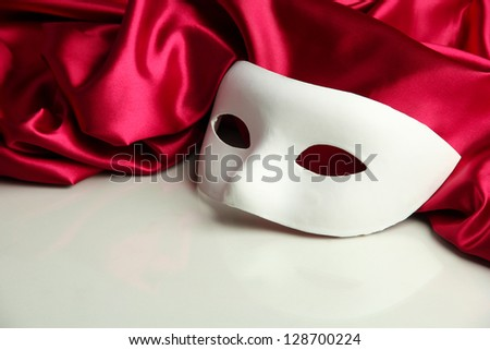 White mask and red silk fabric, isolated on white - stock photo