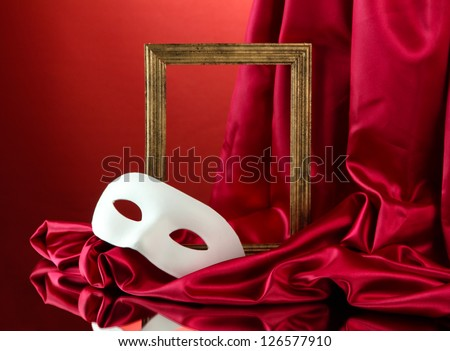 White mask, empty frame and golden silk fabric, on red background - stock photo