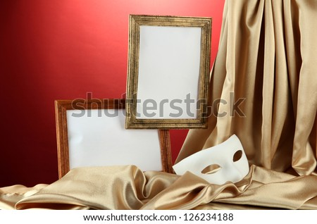 White mask, empty frames and golden silk fabric, on red background - stock photo