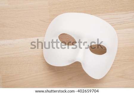 White mask in close up on wooden table. Still life of theatre, carnival or masquerade. Can also be a concept for hiding behind a disguise, a mystery or a tragedy. - stock photo
