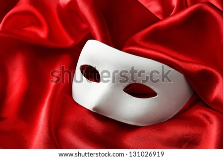 White mask, on red silk fabric