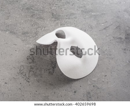 White mask on stone table. Still life of theatre, carnival or masquerade. Can also be a concept for hiding behind a disguise, a mystery or a tragedy. - stock photo