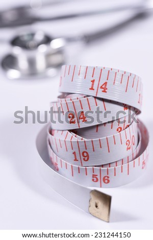 White measure tape and stethoscope isolated on white background.