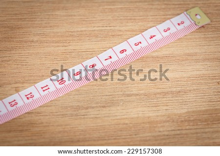 White measure tape on wood texture