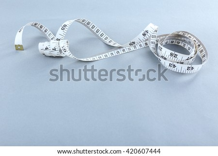 White measuring tape on a grey background