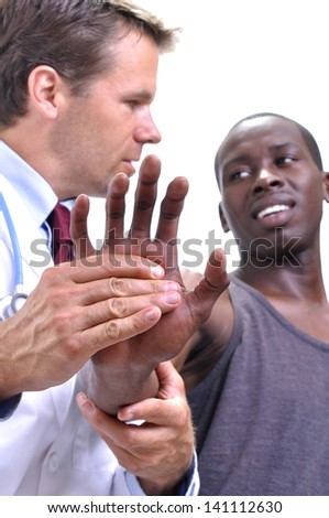 White medical doctor tests pain tolerance of young athletic black man's wrist on white background - stock photo