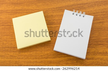 White Memo Note and Sticky Postit on Brown Wooden Surface - stock photo
