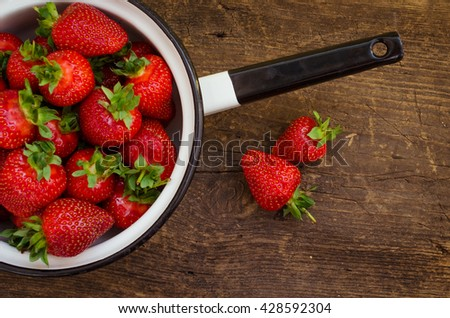White metal colander filled with succulent juicy fresh ripe red strawberries on an old textured table top. Background from freshly harvested strawberries. Directly above. Top view. Horizontal. - stock photo