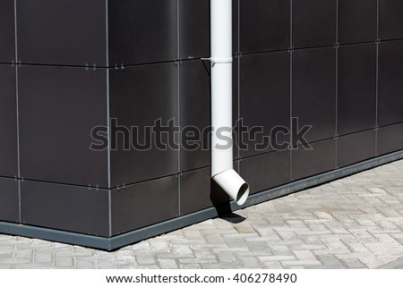 white metal downspout on dark wall of modern building facade - stock photo