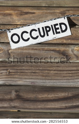 white metal sign with the word occupied hanging at a chain  in front of a wooden wall. Concept for all things being occupied