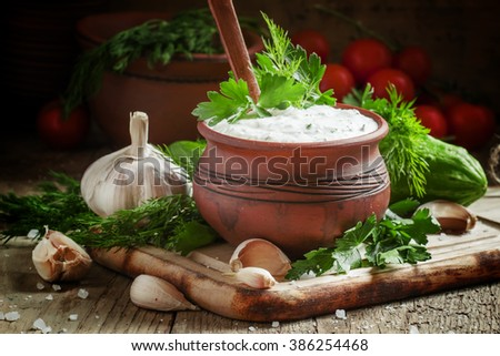 White Middle East sauce with cucumber, yoghurt, garlic and fresh herbs, to meat dishes, in a clay pot, selective focus - stock photo