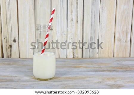 white milk in glass milk bottle with red and white striped straw on whitewashed wood - stock photo