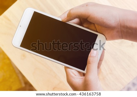 white mobile phone on woman hand with keyboard background, close-up
